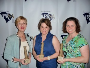 Central Carolina Community Foundation CEO JoAnn Turnquist (left) and Director of Communications Tonia Cochran (right) join Kelly Davis (center) in displaying the three awards won for the Foundation.